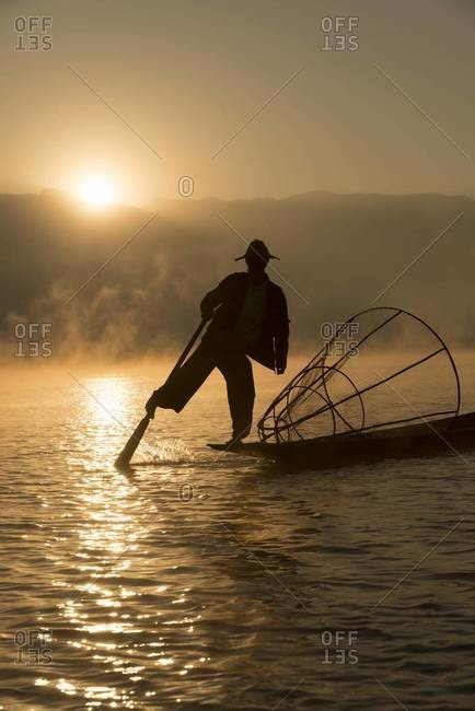 Leg rowing fisherman at sunset on the Inle Lake, Myanmar