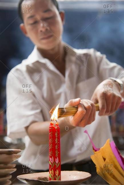 Ho Chi Minh City, Vietnam - March 25,2013: Man lighting a bunch of incenses in a temple