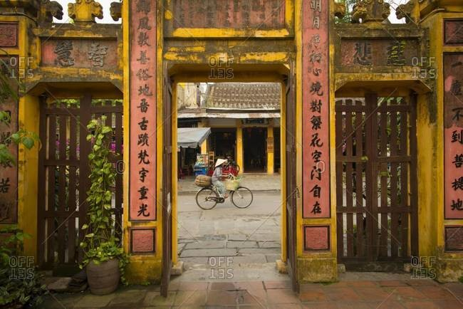 Hoi An, Vietnam - March 26,2013: Woman riding a bicycle between the gates of a temple and cafe