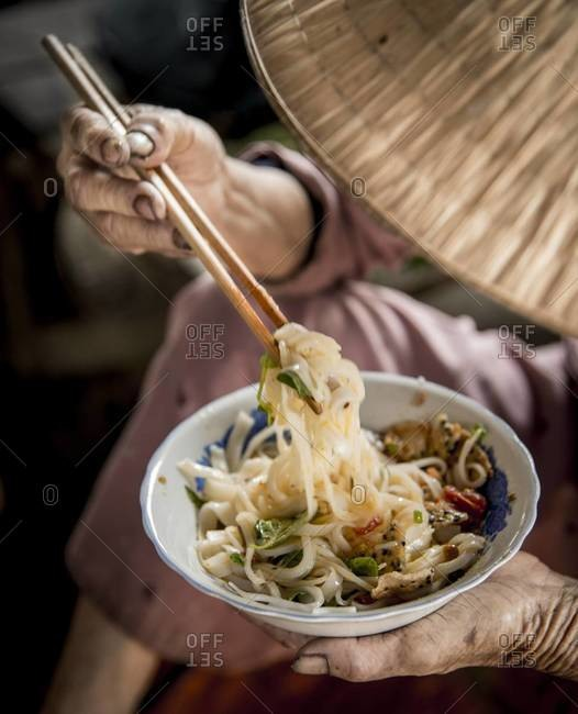 High angle view of a Vietnamese man eating noodles