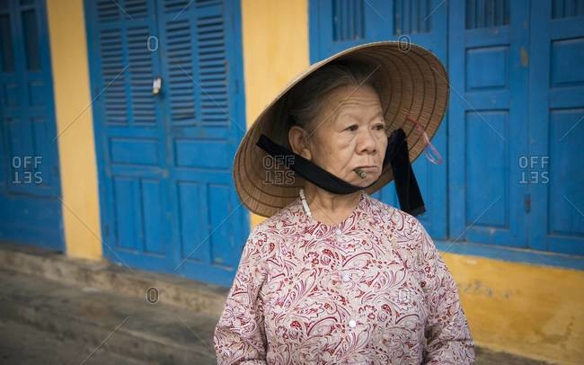 Hoi An, Vietnam - March 28,2013: Elderly woman smoking a cigar