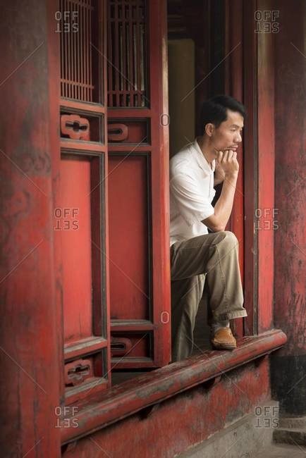 Hanoi, Vietnam - March 30,2013: Pensive man looking out the window of a building