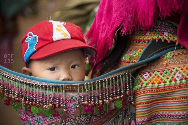 Coc Ly, Vietnam - April 2,2013: Close up of Flower Hmong woman carrying her child on her back