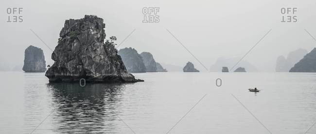 Fisherman rowing a boat at Ha Long Bay, Vietnam
