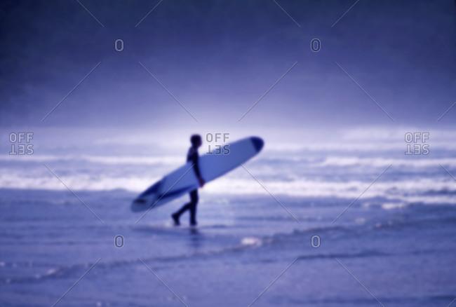 Surfer walking on beach - Offset
