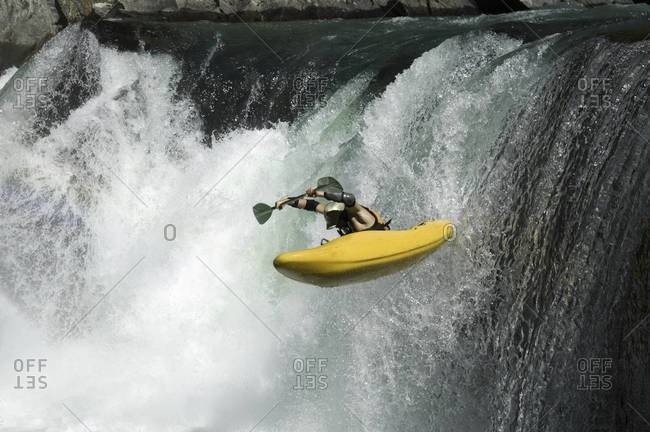 Male kayaker going over a waterfall