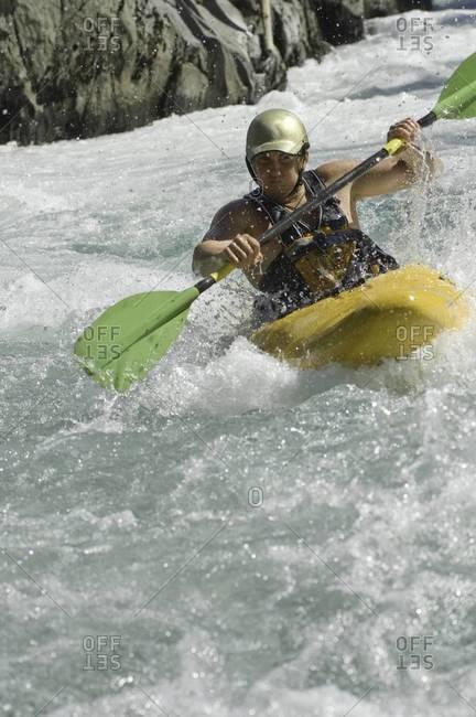 Male kayaking rough waters in white water kayak