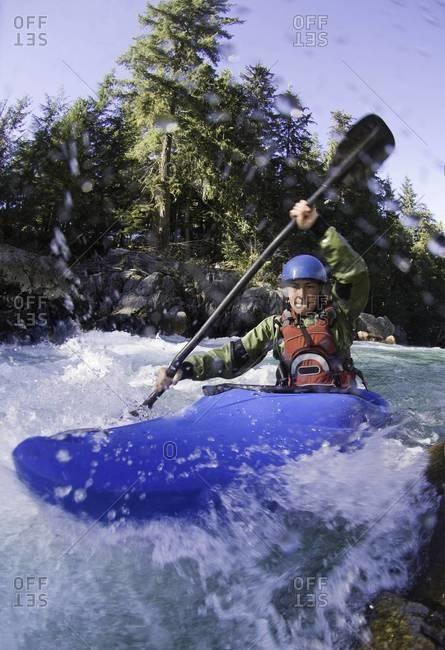 Woman kayaking rough waters