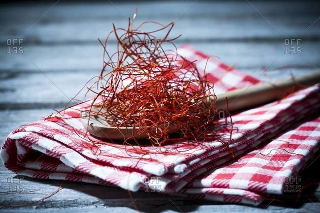 Wooden spoon with chili threads on kitchen towel and wooden table