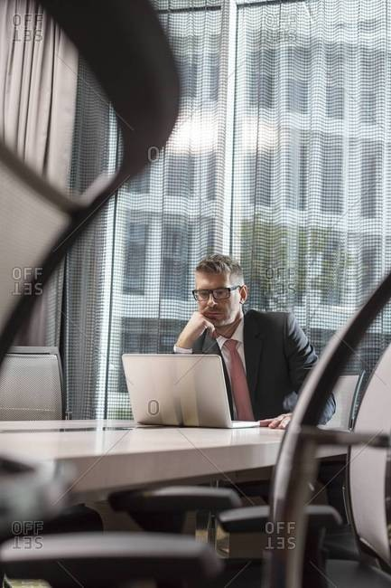 Poland, Warzawa, businessman sitting at conference table in hotel using laptop