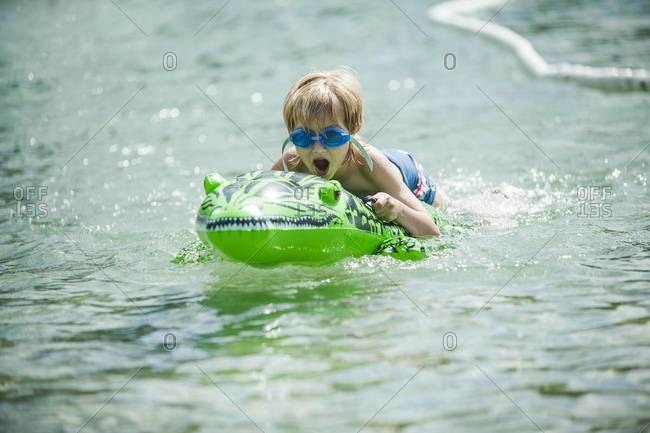 Young boy with swimming goggles and swim toy