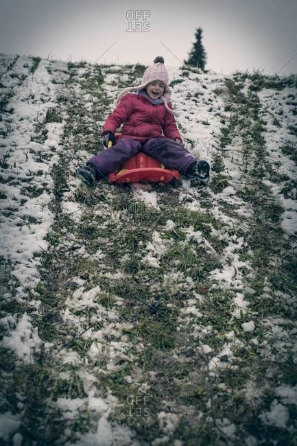 Germany, Bavaria, Landshut, laughing  little girl tobogganing