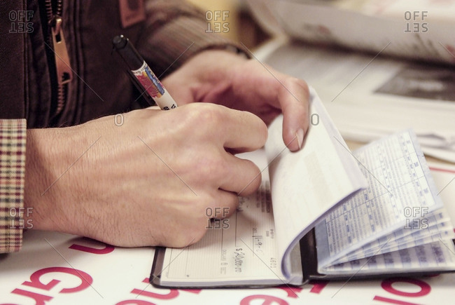 Close up of hand writing a $20,000 check