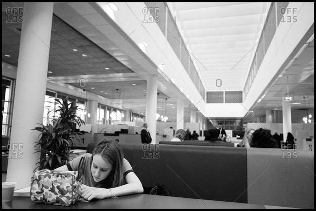 Girl writing on desk while sitting in hall