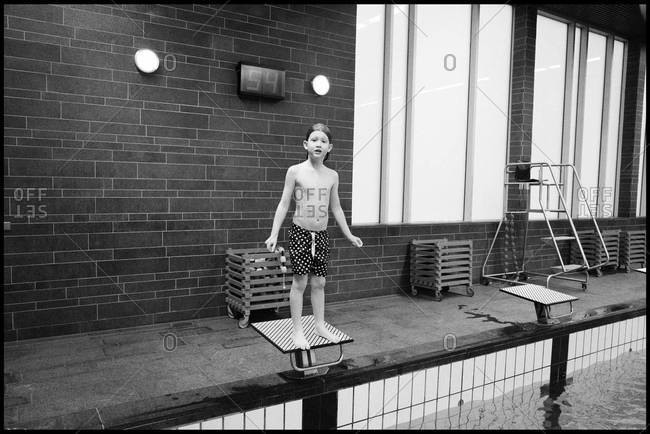 Boy standing on swim start in swimming pool ready to jump