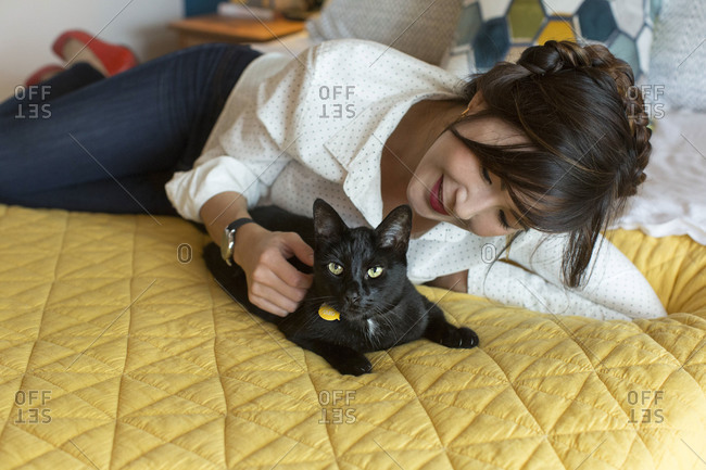 Black cat and woman on bed in bedroom