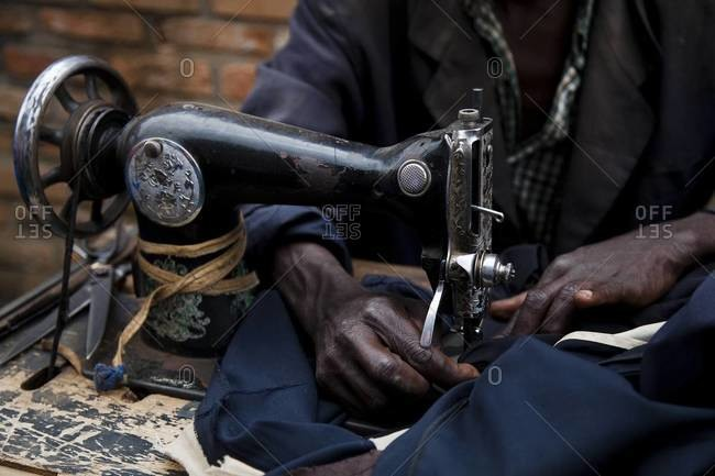Close up of African man working with a sewing machine