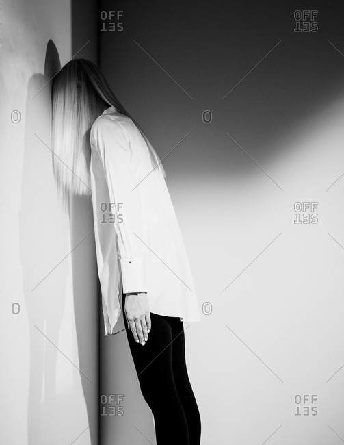 Fashionable woman leaning face forward against a wall