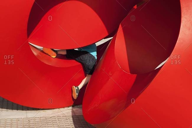 Child playing on red modern sculpture, Spain