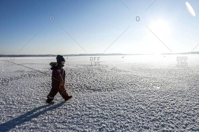 Little boy walking in the snow in Nacka, Sweden