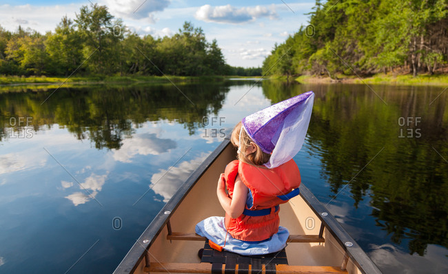 Young girl wearing princess costume in a canoe