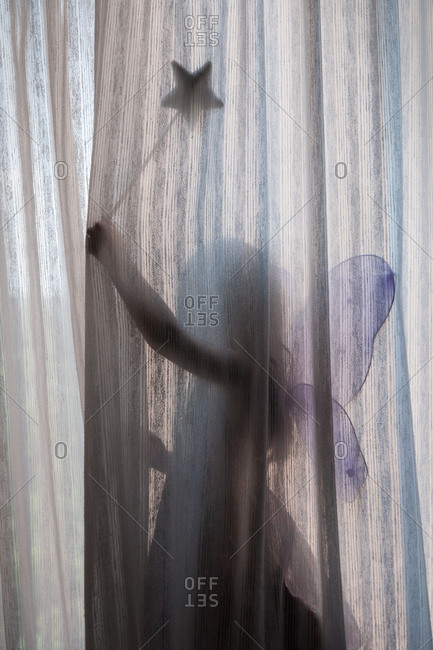Young Girl wearing fairy costume behind curtains