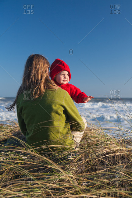 Mother and toddler daughter on beach in autumn