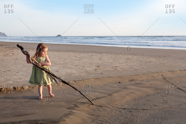 Young girl draw a line in the sand