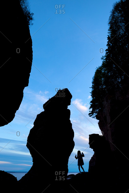 Silhouette of girl among sea stacks