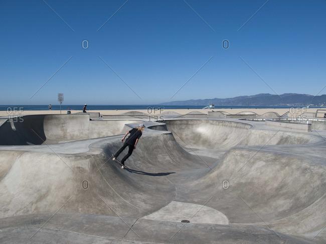 Man skateboarding in skateboard park, Venice Beach, California