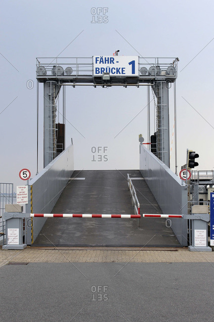 A bridge used to load cars onto a ferry, with German language sign