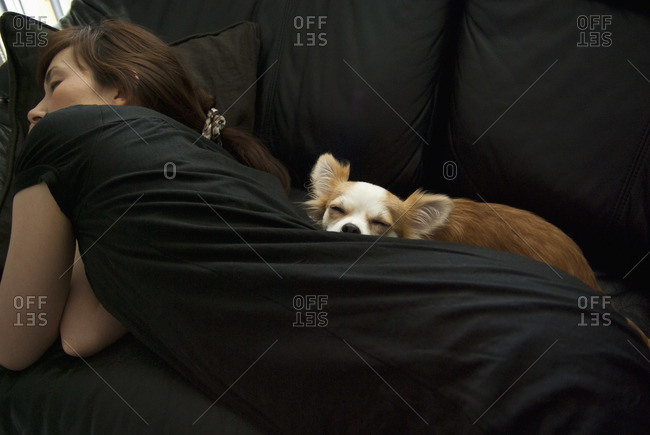 A woman with dog sleeping on a sofa
