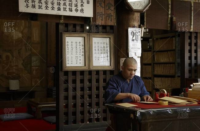Buddhist monk working at the desk in a temple, Kii Mountains, Japan