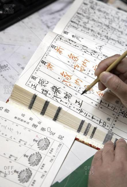 Close up of man writing with a bamboo pen
