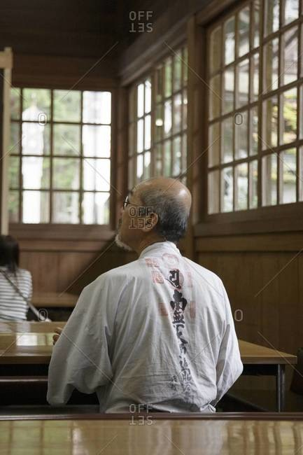 Back view of Japanese man sitting in a Buddhist temple