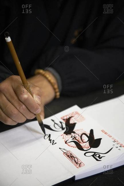 Man writing in a Japanese temple book