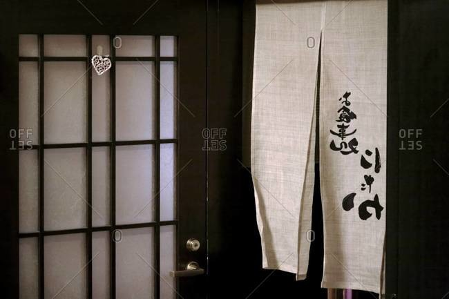 Fabric with kanji hanging by a door