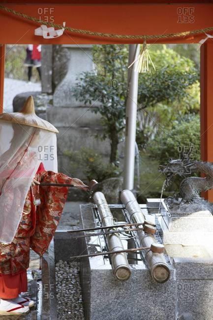 Pilgrim wearing a Heian era kimono rinsing hands before entering temple