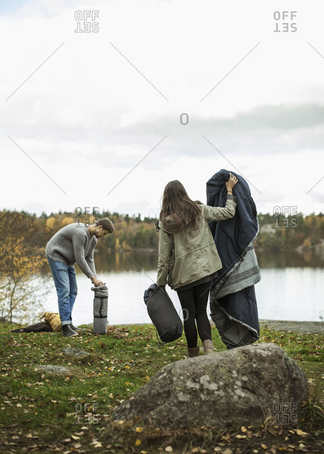 Young couple with blanket and sleeping bag at lakeshore