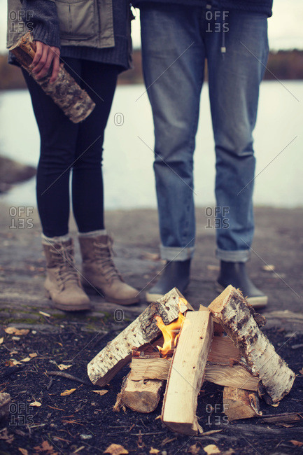 Low section of couple standing by campfire