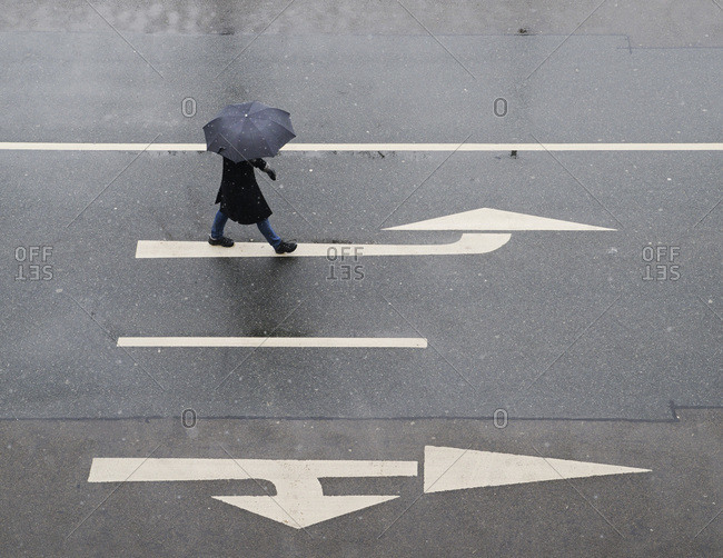 High angle view of woman with umbrella walking on road