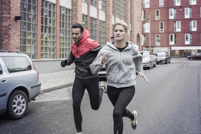 Sporty couple running on street