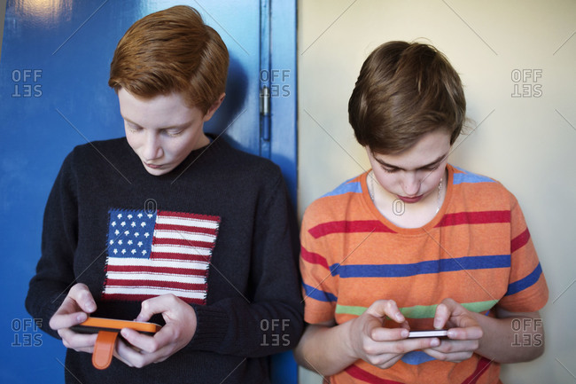 School students using mobile phones in the hallway