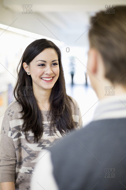 Happy female student conversing with friend in college