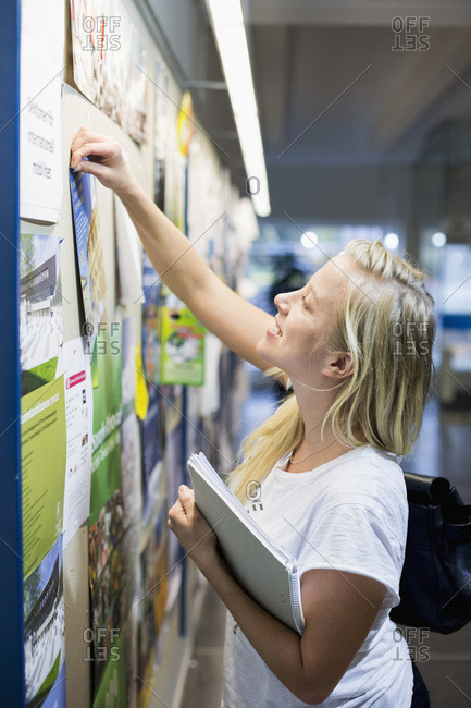 University student tacking paper to bulletin board in college