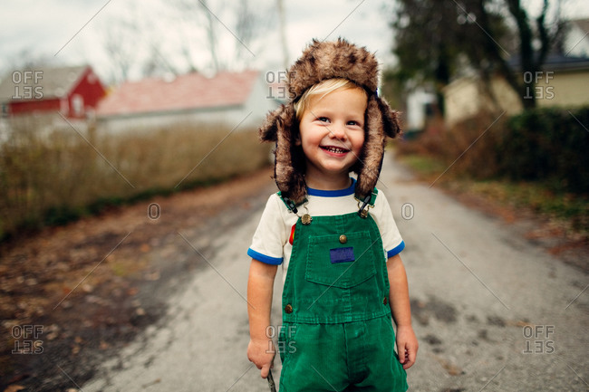 Toddler boy in flap ears standing on road