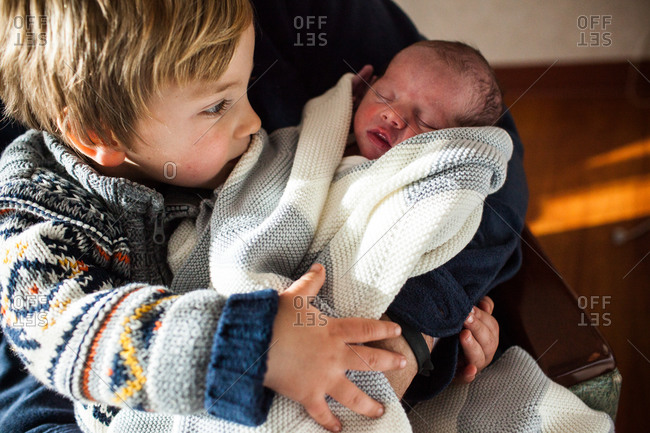 Little boy sitting on father's lap adoring newborn sibling