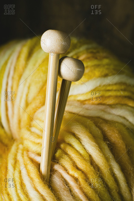 Hand dyed yellow wool yarn and knitting needle