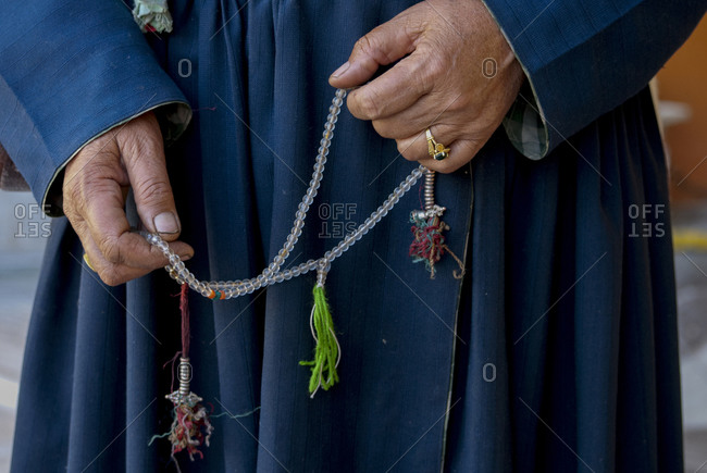 Person\'s hands holding prayer beads