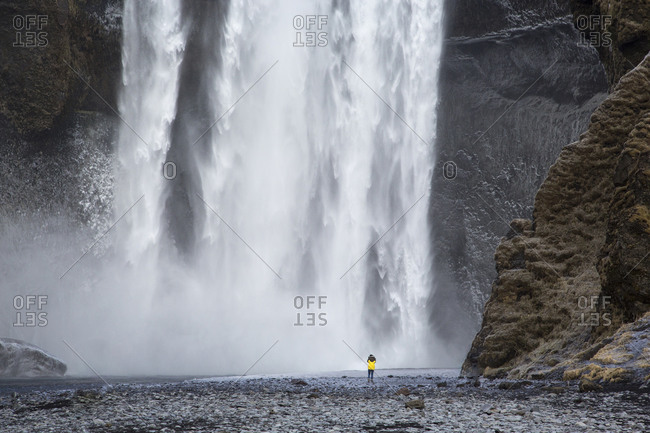 Person in front of Skogafoss waterfall